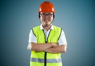 Young asian construction workers in safety helmet ,isolated on blue background .